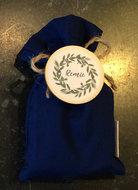 blauw zakje in stof met houten badge met wasknijper